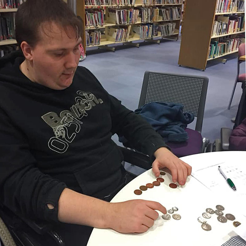 Student pursuing his individual outcomes by learning how to count money at Green Days Day Care