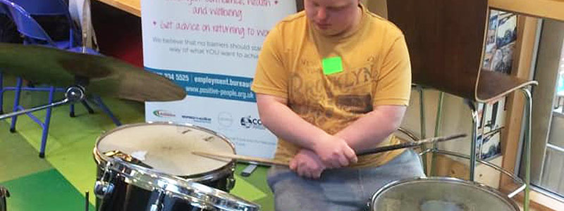 Man learning to play the drums with Green Days Day Care
