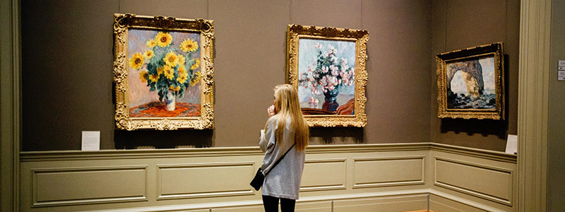Woman looking at art in a museum - Green Days Day Care