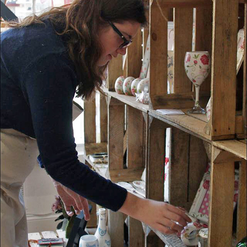 Shop Assistant learning transferrable skills filling a shelf at Green Days Shop Taunton